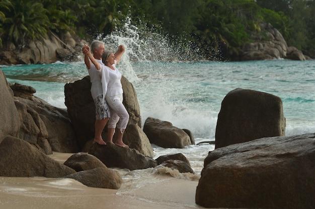 Heureux couple de personnes âgées reste à la plage tropicale avec les mains vers le haut