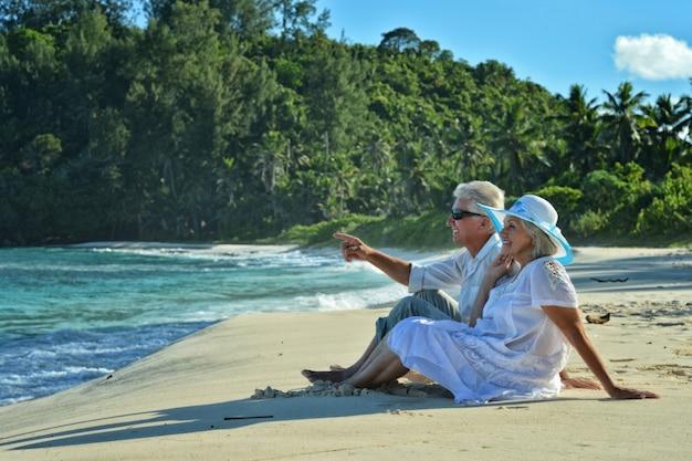 Heureux couple de personnes âgées reste à la plage tropicale