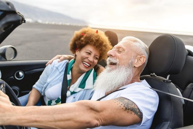 Heureux couple de personnes âgées s'amusant en voiture décapotable pendant les vacances d'été
