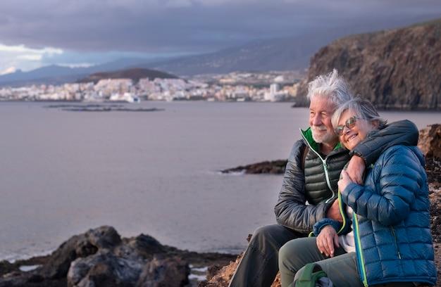 Heureux couple de personnes âgées s'embrasse tout en étant assis sur tcliff un jour d'hiver en profitant du plein air