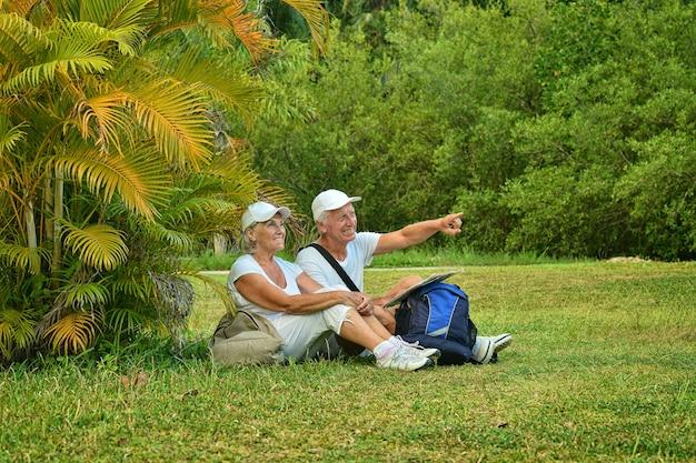 Heureux couple de personnes âgées avec des sacs à dos dans un jardin tropical en plein air