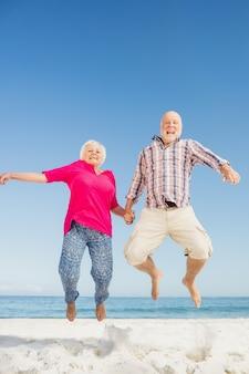 Heureux couple de personnes âgées sautant