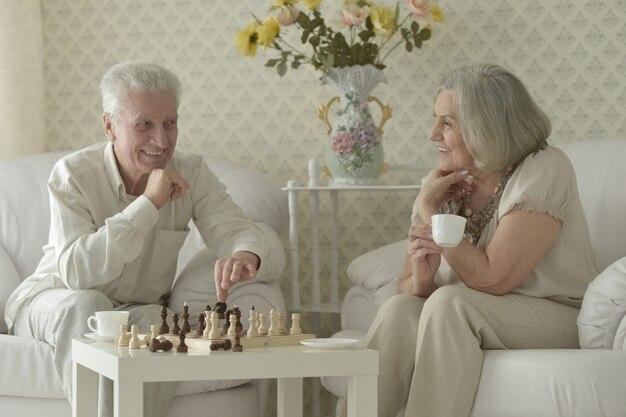 Heureux couple de personnes âgées se reposant à la maison et jouant aux échecs