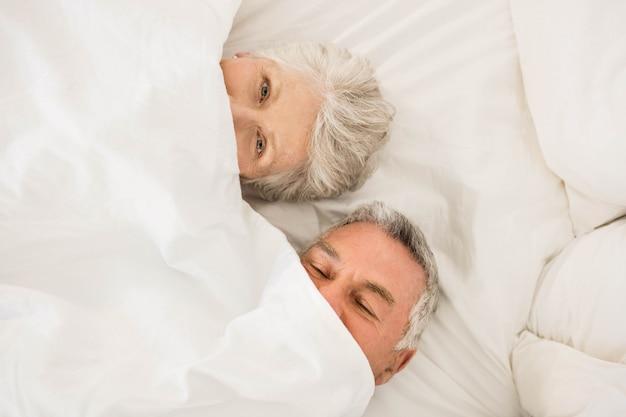 Heureux couple de personnes âgées sous une couette dans son lit en regardant la caméra
