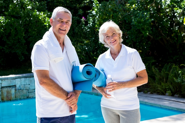 Heureux couple de personnes âgées avec des tapis d'exercice au bord de la piscine