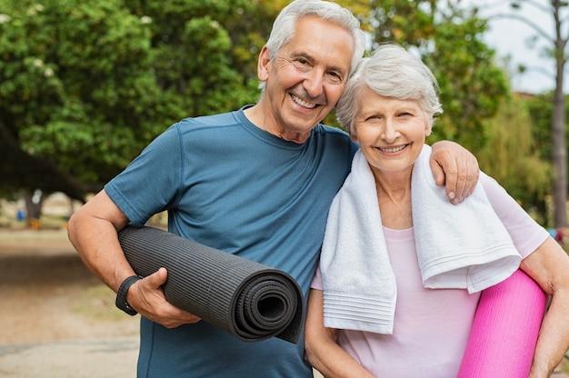 Heureux couple de personnes âgées avec tapis de yoga