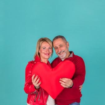 Heureux couple de personnes âgées tenant grand coeur rouge