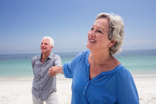 Heureux couple de personnes âgées tenant la main sur la plage