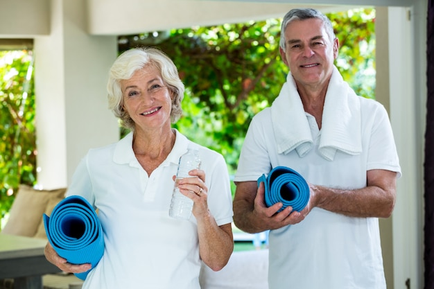Heureux couple de personnes âgées tenant des tapis d'exercice
