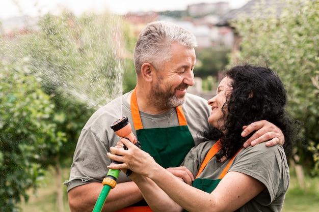 Heureux couple de personnes âgées avec un tuyau d'arrosage