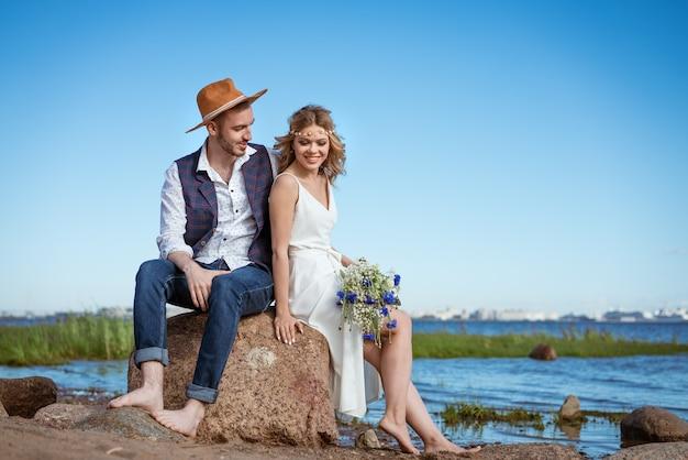 Heureux couple sur la plage journée d'été tenant un bouquet de fleurs à la main