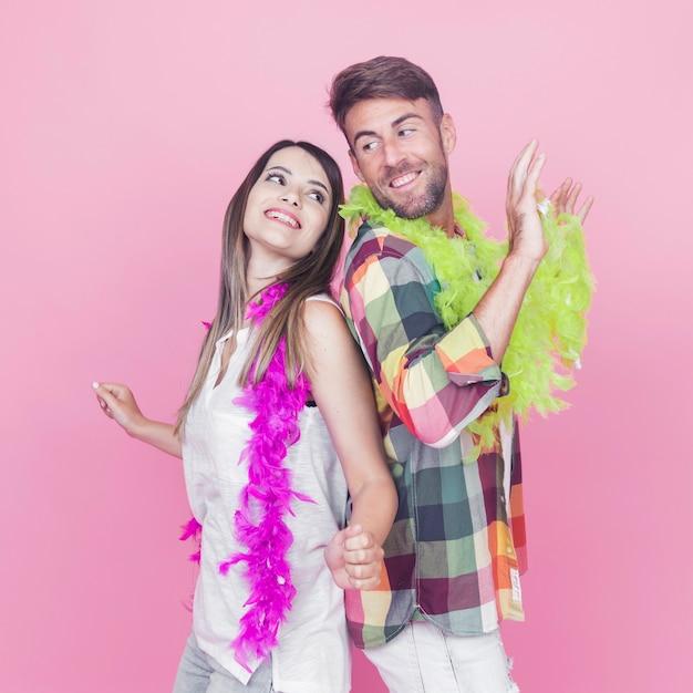 Heureux couple portant le boa autour de leur cou danser ensemble