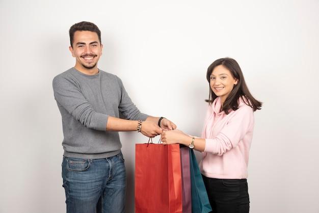Heureux couple portant des sacs à provisions sur blanc.