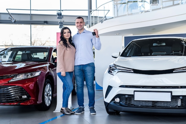 Heureux couple posant avec les clés de la nouvelle voiture