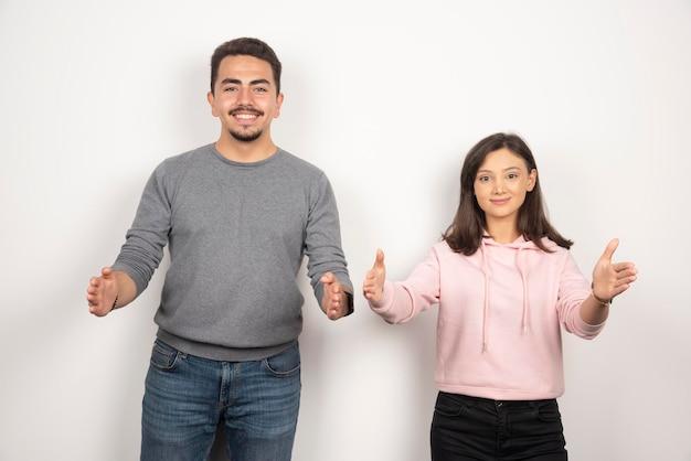 Heureux couple posant contre le blanc.