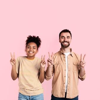 Heureux couple posant avec le signe de la paix