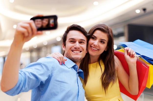 Heureux couple prenant une photo lors d'un shopping