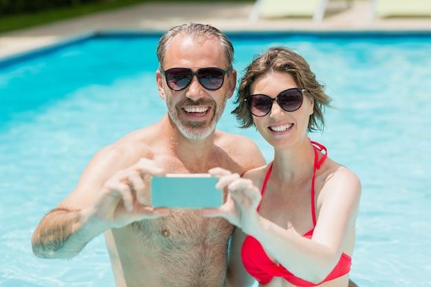 Heureux couple prenant selfie du téléphone mobile dans la piscine