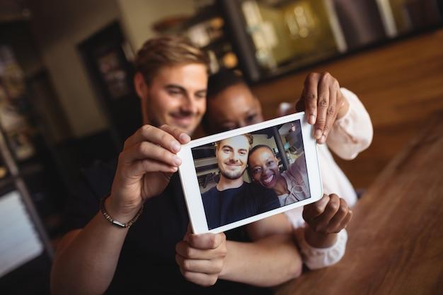 Heureux couple prenant selfie de tablette numérique