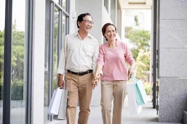 Heureux couple profitant des vacances, ils se tiennent la main en marchant le long de la rue après le shopping