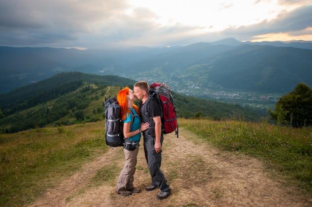 Heureux couple randonneurs s'embrasse sur la route en montagne.