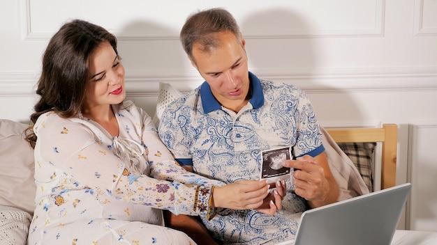 L'heureux couple regardant bébé scan