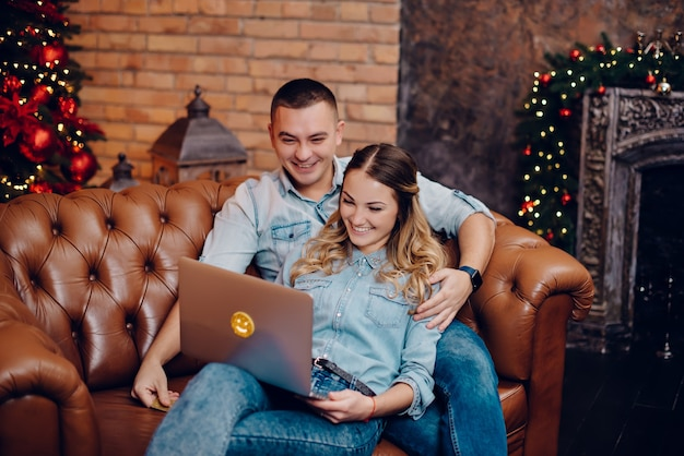 Heureux couple regardant moniteur d'ordinateur portable sur des décorations de noël