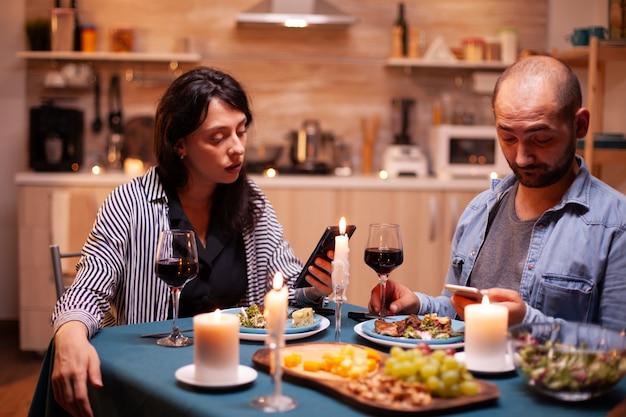 Heureux couple regardant une vidéo sur smartphone dans la cuisine pendant l'anniversaire. des adultes assis à table dans la cuisine naviguant, cherchant, utilisant des smartphones, internet, célébrant un anniversaire.