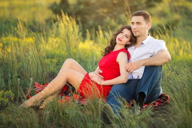 Heureux couple reposant sur l'herbe dans le parc