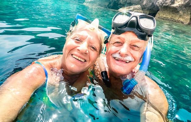 Heureux couple de retraités avec masque de plongée prenant selfie lors d'une excursion tropicale