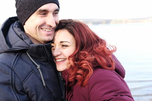 Heureux couple riant dans une étreinte - famille mari et femme heureux d'être ensemble