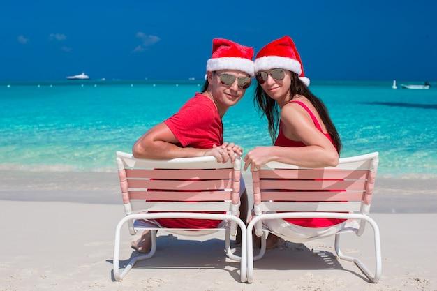 Heureux couple romantique en chapeaux rouges sur la plage tropicale