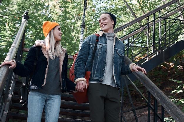 Heureux couple romantique de touristes descendent et se tiennent la main sur les marches