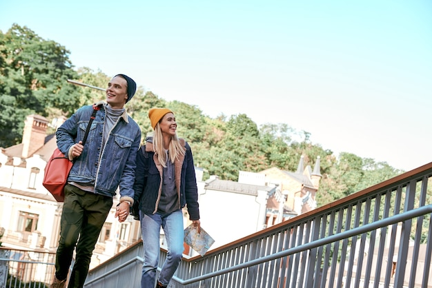 Heureux couple romantique de touristes se tiennent la main sur les marches
