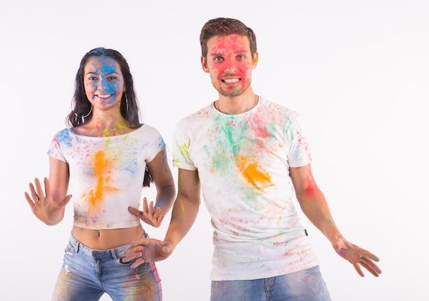 Heureux couple s'amusant recouvert de peinture sur mur blanc