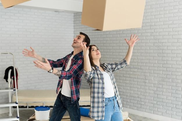Heureux couple s'amuse avec des boîtes en carton dans une nouvelle maison au jour du déménagement