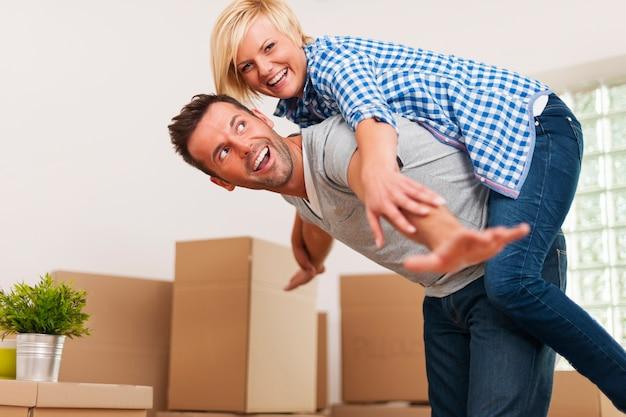 Heureux couple s'amuse dans leur nouvel appartement