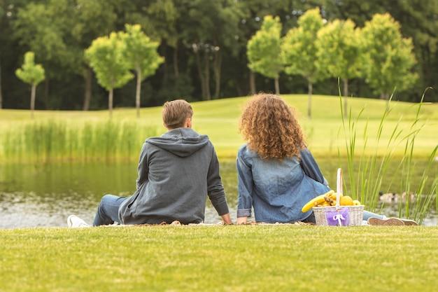L'heureux couple s'assoit dans un parc près du lac