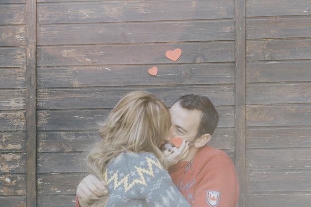 Heureux couple s'embrassant au mur en bois