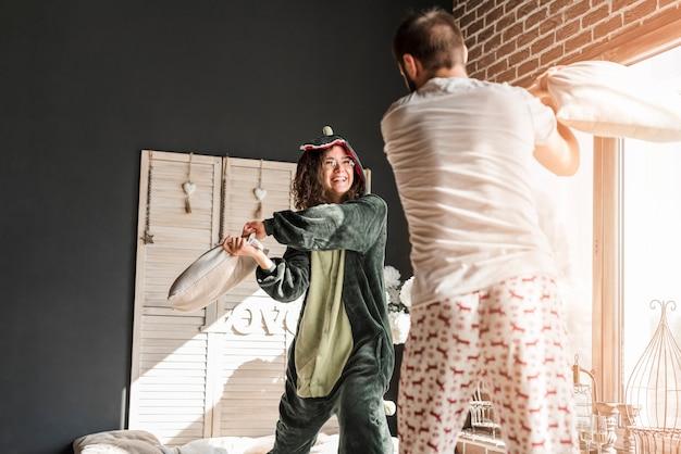 Heureux couple se battre avec des oreillers à la maison