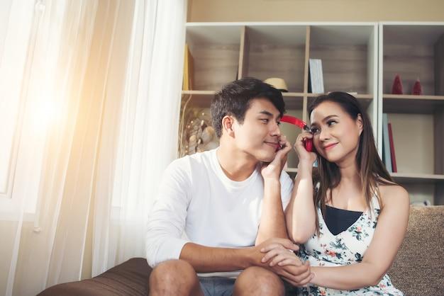Heureux couple se détend et joue ensemble dans le salon.
