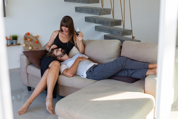 Heureux couple se détendre, boire du vin et parler assis sur le canapé. moments romantiques à la maison.