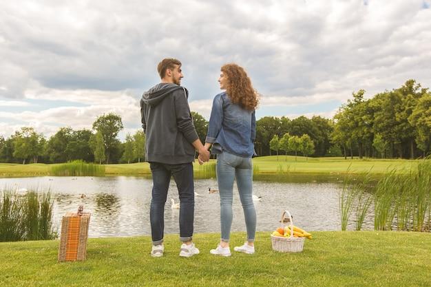 L'heureux couple se tient dans un parc près du lac