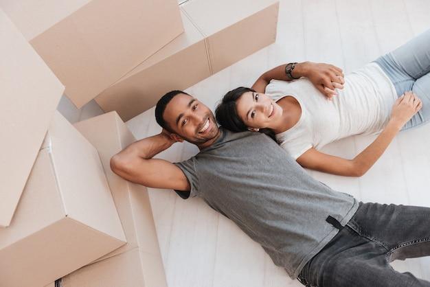 L'heureux couple se trouve sur le sol avec des boîtes non emballées. en regardant de face.