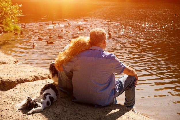 Heureux couple senior assis sur le lac au soleil avec leurs chiens. concept de vacances en famille dans la nature