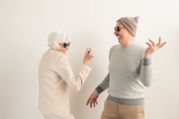 Heureux couple senior occasionnel dans des lunettes de soleil s'amusant et dansant