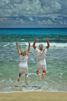Heureux couple senior sautant en été au bord de la mer
