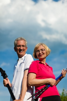 Heureux couple senior ou senior faisant de la marche nordique en été