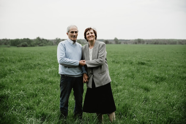 Heureux couple senior souriant amoureux de la nature, s'amuser. couple de personnes âgées sur le terrain vert. joli couple de personnes âgées marchant et serrant dans la forêt de printemps