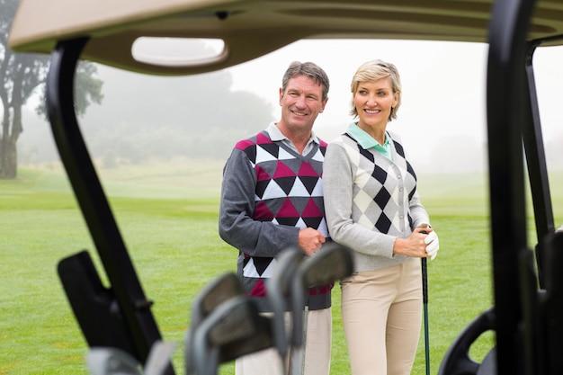Heureux couple souriant au golf